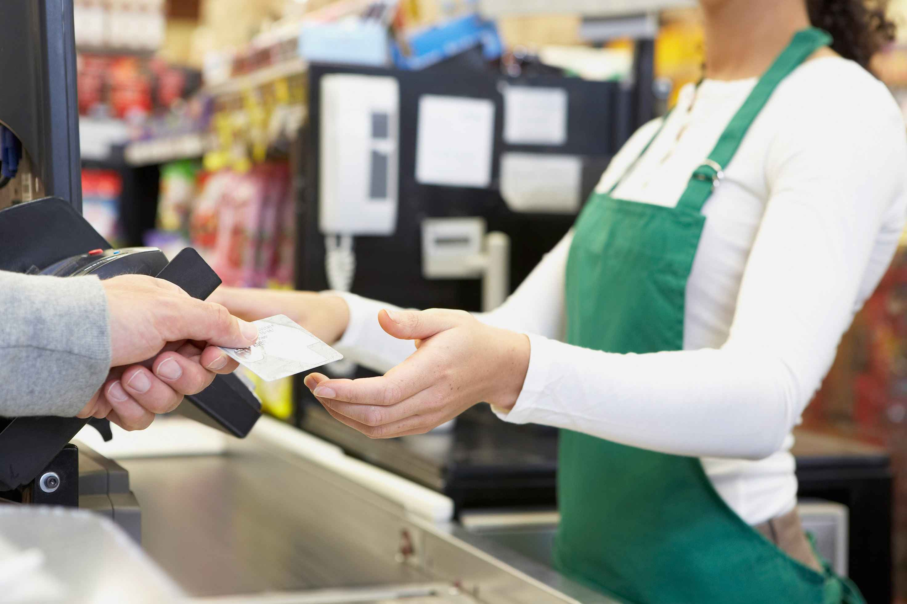 "Vancouver, """", Canada --- Man paying with credit card at grocery store --- Image by © Noel Hendrickson/Blend Images/Corbis"